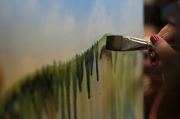 Artist painting a green landscape